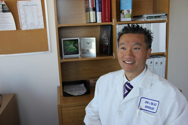 Dr. John Sim in front of bookcase.