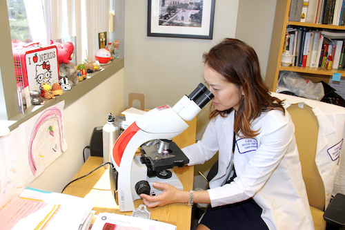 Dr. Helen Moon looking into microscope.