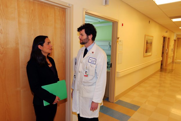 Dr. Sara Tartof and Dr. Bruno Lewin discuss vaccine research in hallway at the Los Angeles Medical Center